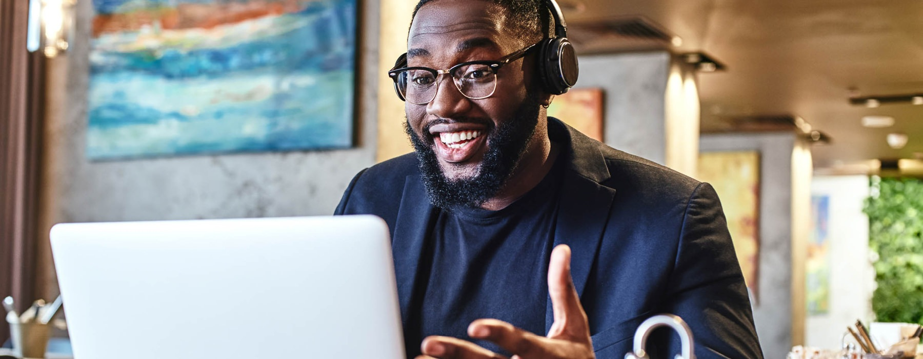 happy man with headphones on video conferences on his laptop